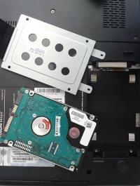 Chcąc zamontować twardy dysk w laptopie, musisz przykręcić go najpierw do wspornika, a potem wsunąć do wnęki w obudowie.